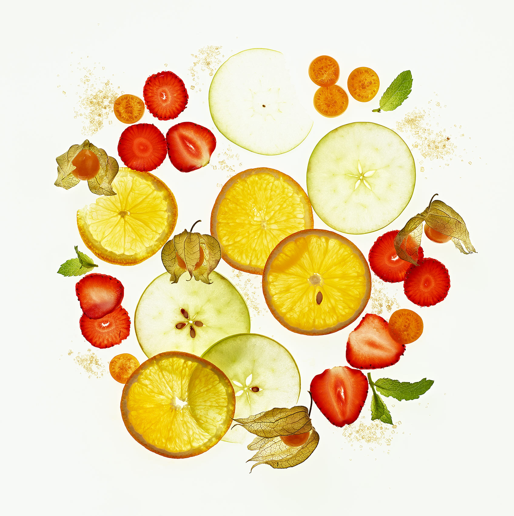 a fruit salad of oranges apples strawberies and cape gooseberry laid out on a backlit white background